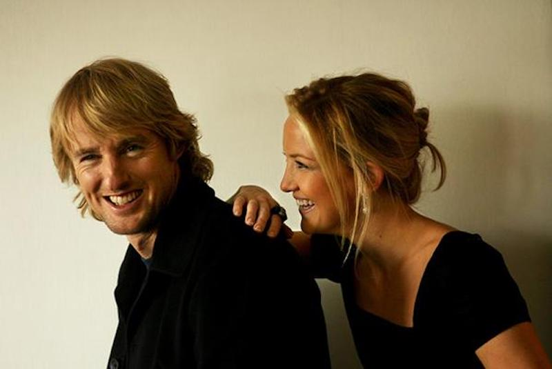 Kate Hudson leans on Owen Wilson's back while the two smile playfully during a photoshoot.