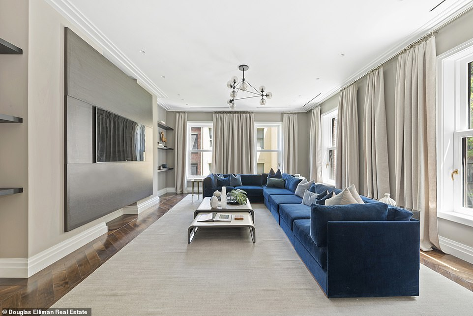 A large, rectangular family room showcases a blue, L-shaped couch to match the L-shape of the windowed walls.