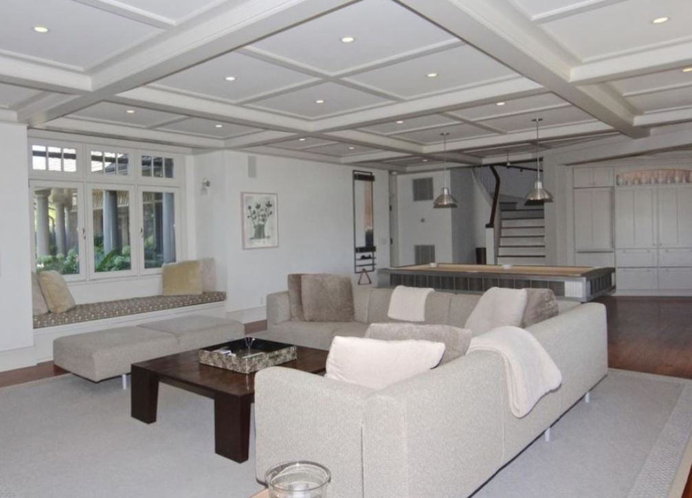 The spacious lounge room with couches, a TV, and a pool table