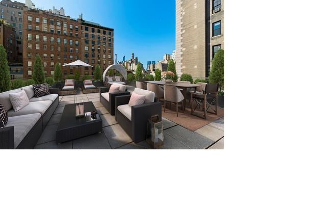 Lounge chairs, a couch, coffee table, two cushed chairs, and a long table reveal an outdoor living space with city views.