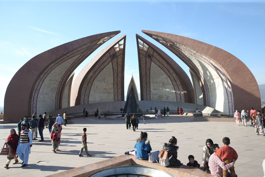 People tour a monument in Islamabad that consists of four pointed arches curved towards one another