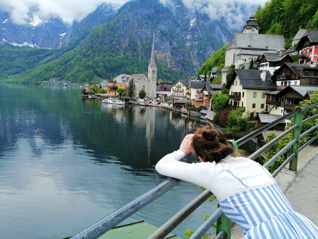 A woman leans forward to photograph a lake in Austria