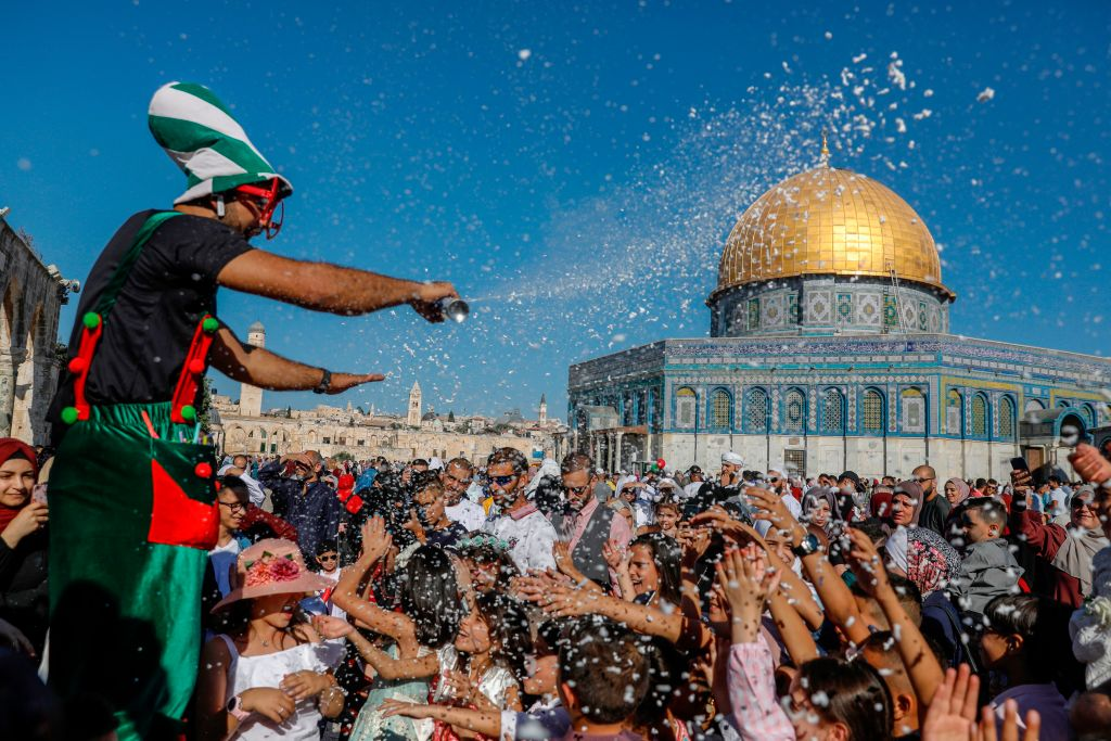 A crowd is gathered infront of the Dome of Rock mosque where they're entertained by a clown