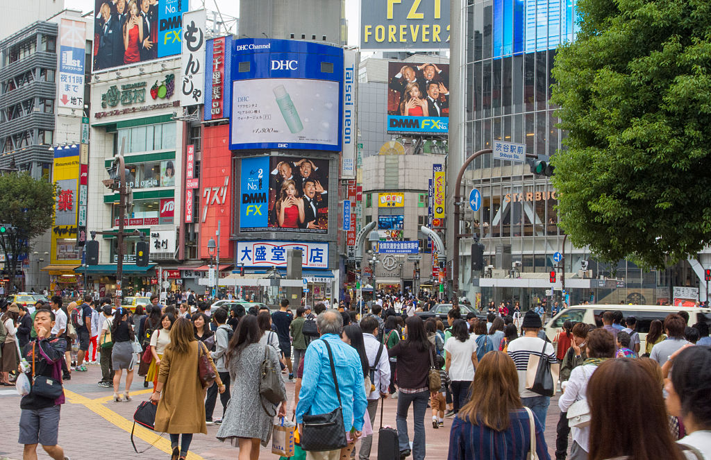 Tokyo Japan crowds rush moving walking in the busy Shibuya Station area