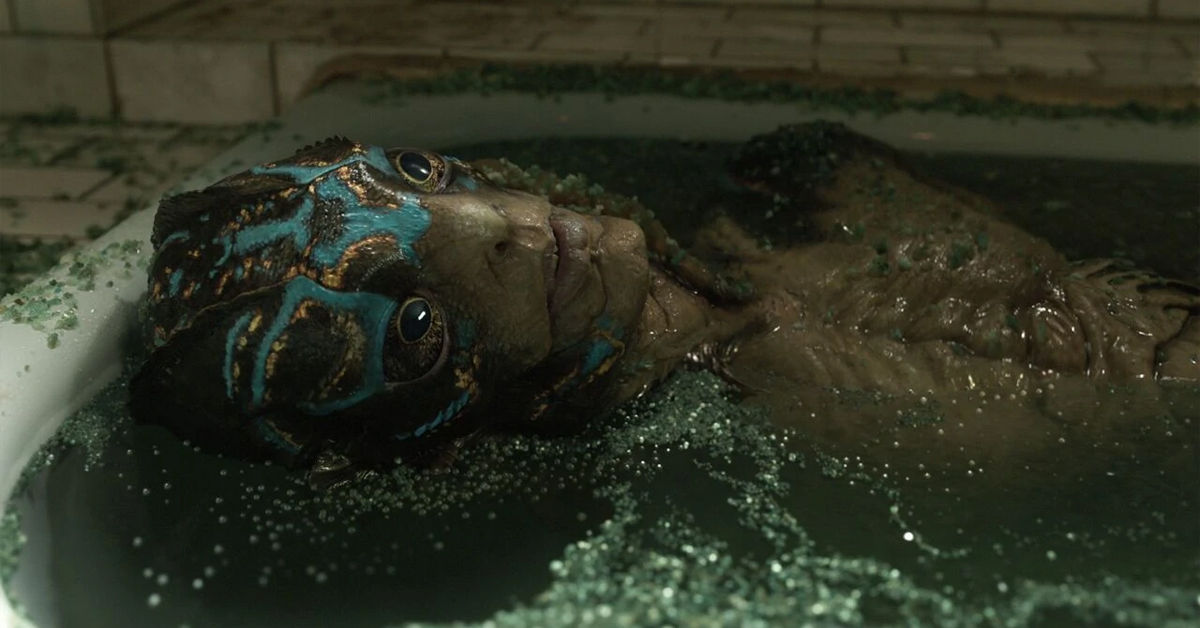 doug jones as the amphibian man in the shape of water. he's laying in a bathtub