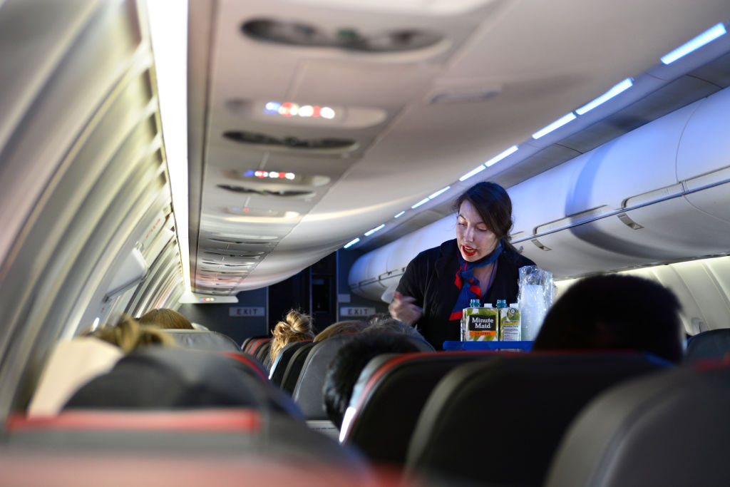 A Flight Attendant Offers Beverages