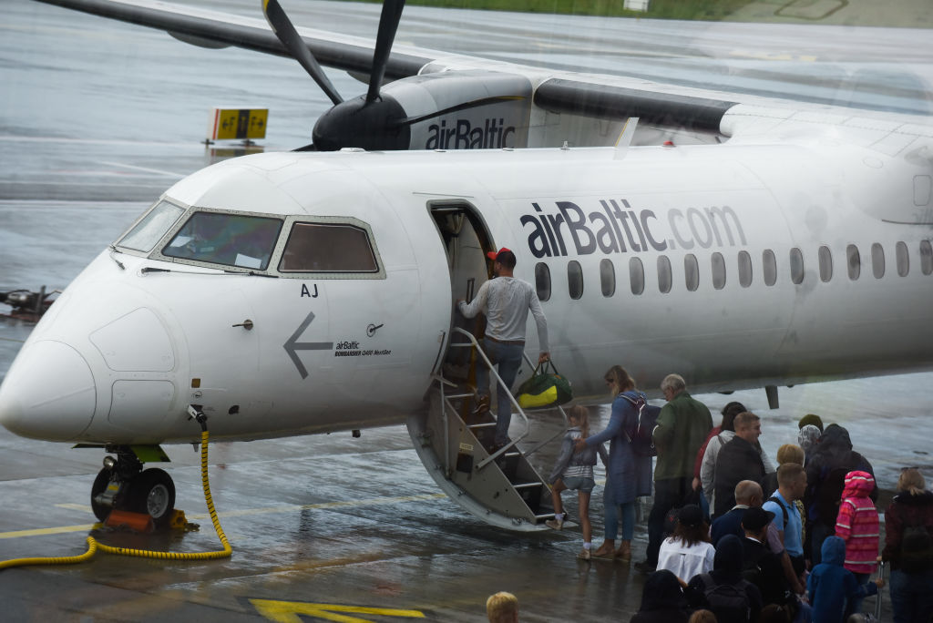 People Board A Plane Outside