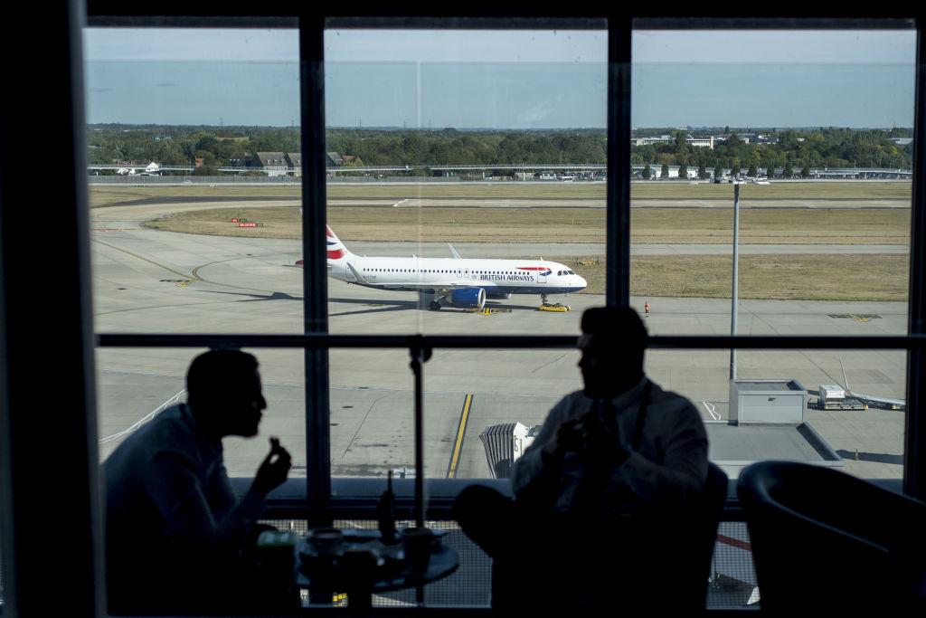 The Silhouette Of Men Talking In An Airport Window