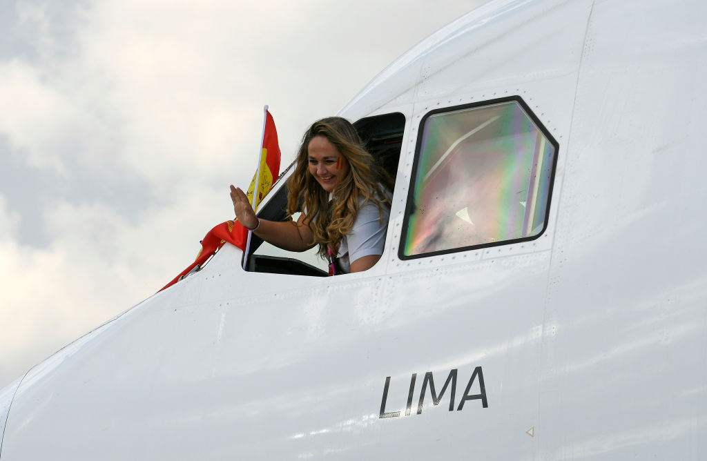 A Female Pilot Waves Out An Airplane Window