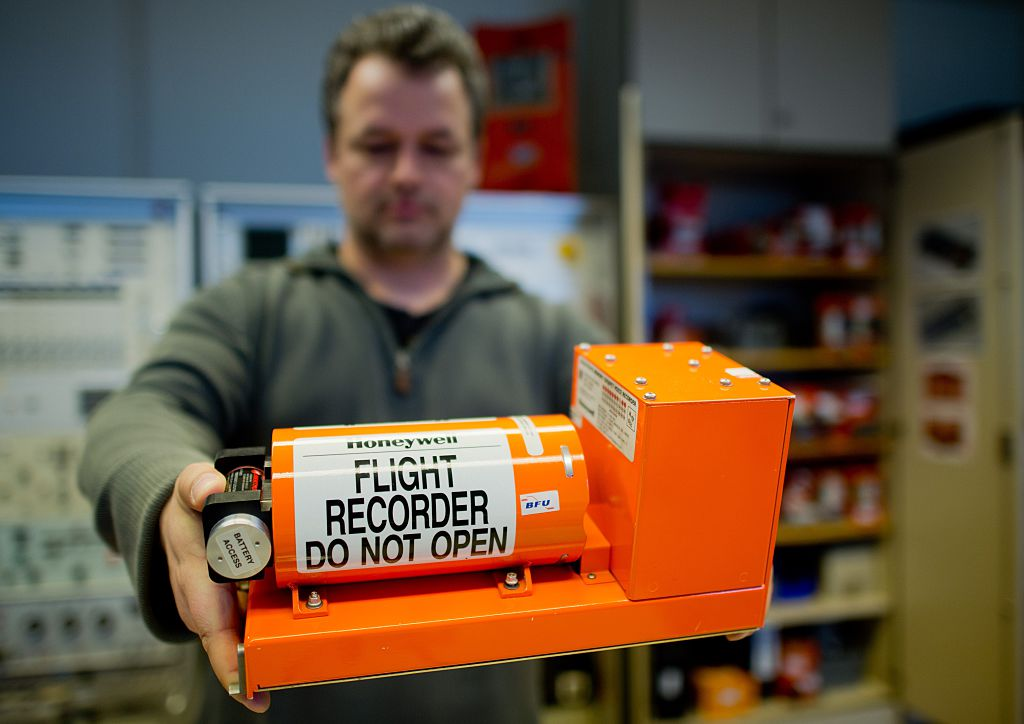 A Man Holds Out A Black Box
