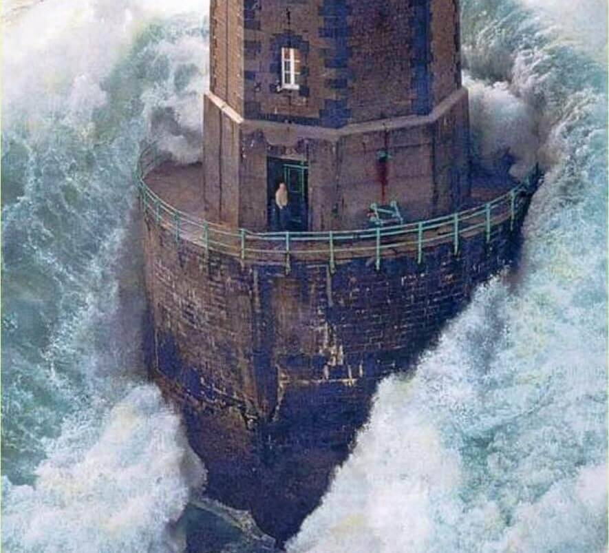 person standing in lighthouse door as large wave hits it
