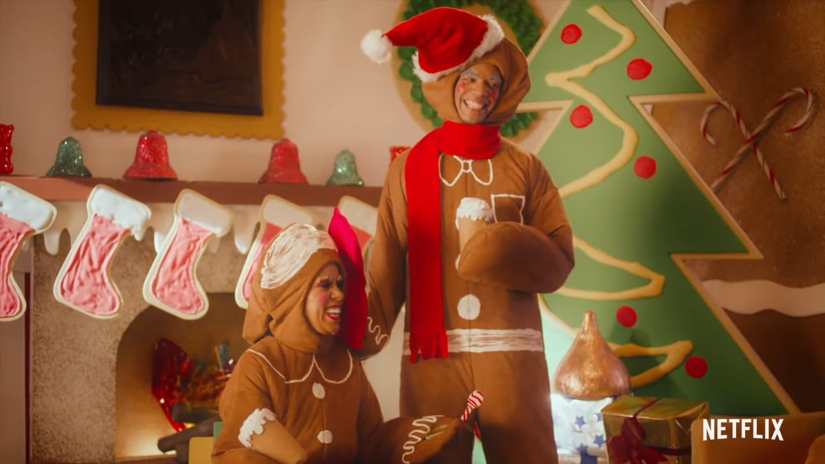 Two actors dressed as gingerbread men wear giant smiles.
