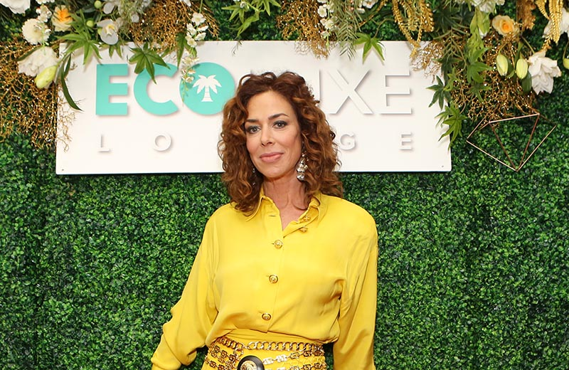 Claudia Wells looks gorgeous as ever while posing in front of a EcoLuxe sign.