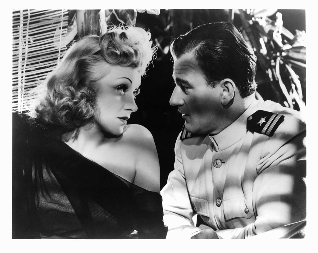 Marlene Dietrich and John Wayne gaze into each others eyes in a scene from the film 'Seven Sinners