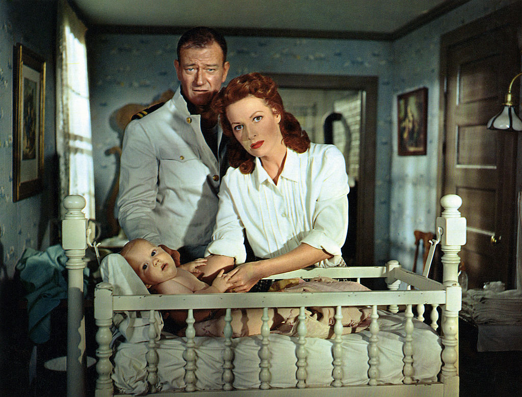 John Wayne and Maureen O'Hara stand over a baby in a crib in a scene from the film 'The Wings Of Eagles
