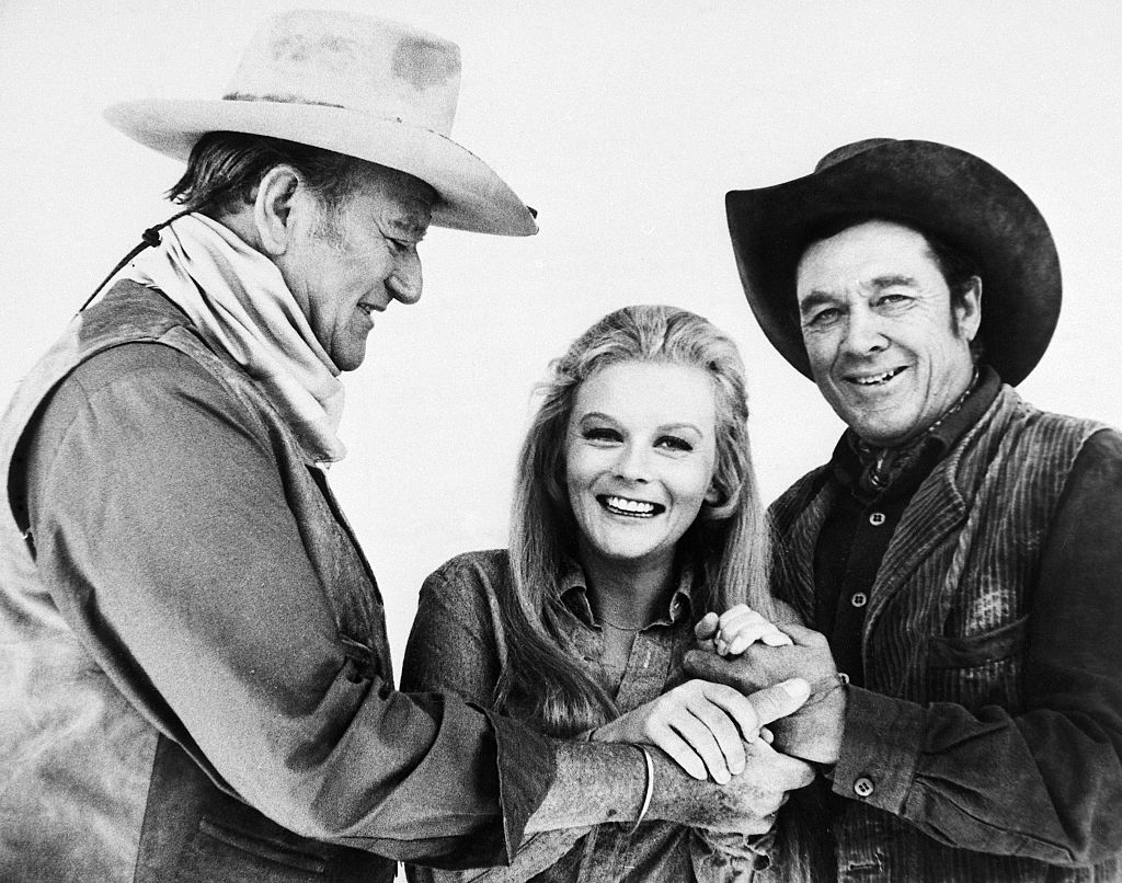 John Wayne, Ann-Margret and Ben Johnson playfully hand-holding during a break in shooting new film on location.