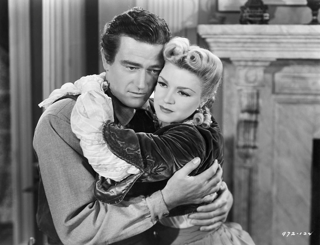 John Wayne and Claire Trevor embracing in Dark Command.