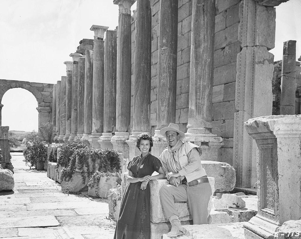 Portrait of actors John Wayne and Sophia Loren amongst Roman ruins