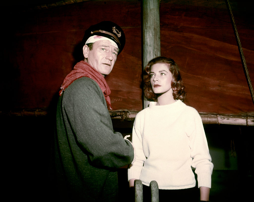 American actors John Wayne and Lauren Bacall on the set of Blood Alley, based on the novel by Albert Sidney Fleischman