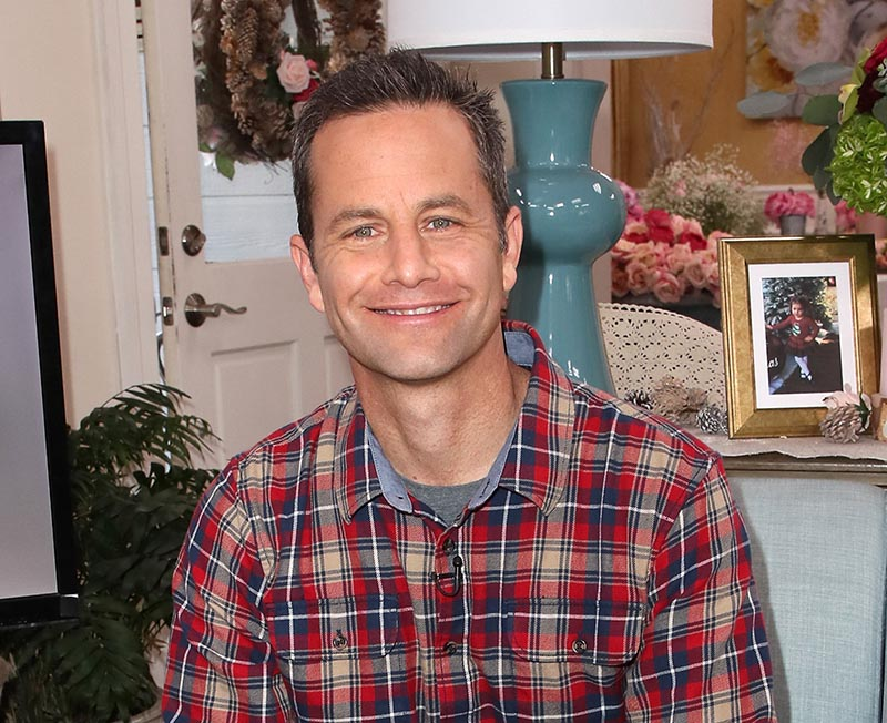 Kirk Cameron smiles while posing in a living room.