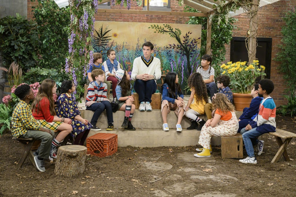 John Mulaney sits in a courtyard amongst children.