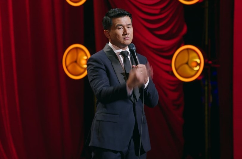Ronny Chieng wears a straight face while doing a hand motion onstage during his special.