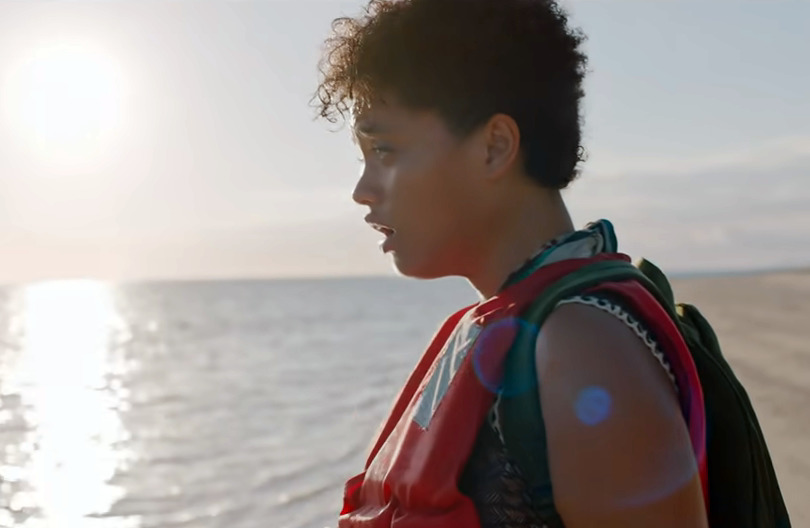 A woman in a lifejacket looks out to sea with her mouth ajar.