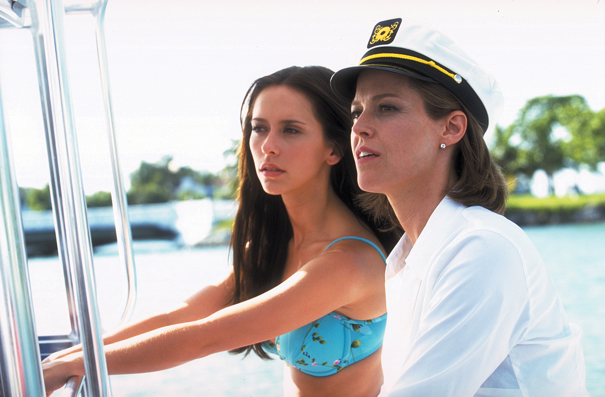 A young woman and her attractive mother ride look at a common point from their seats on a boat.
