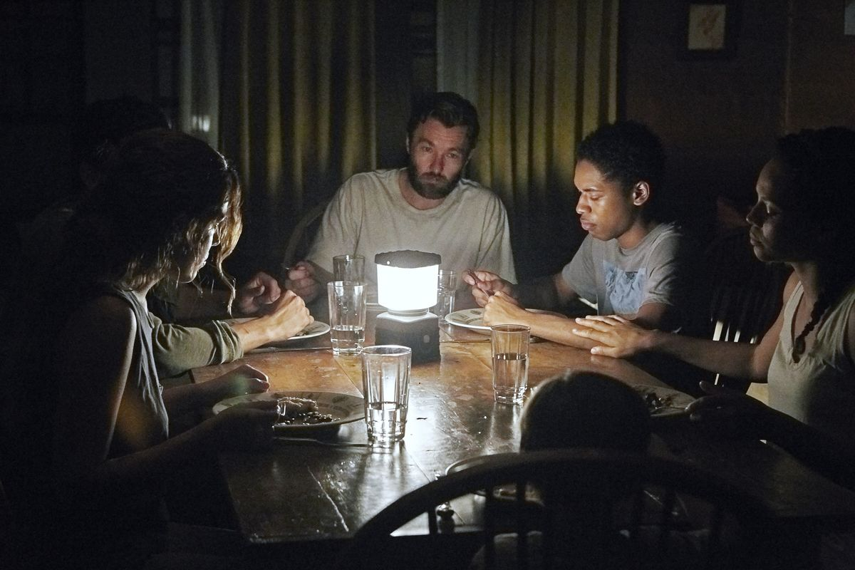 Adults gather around a table that is only lit by a single lamp in its center.