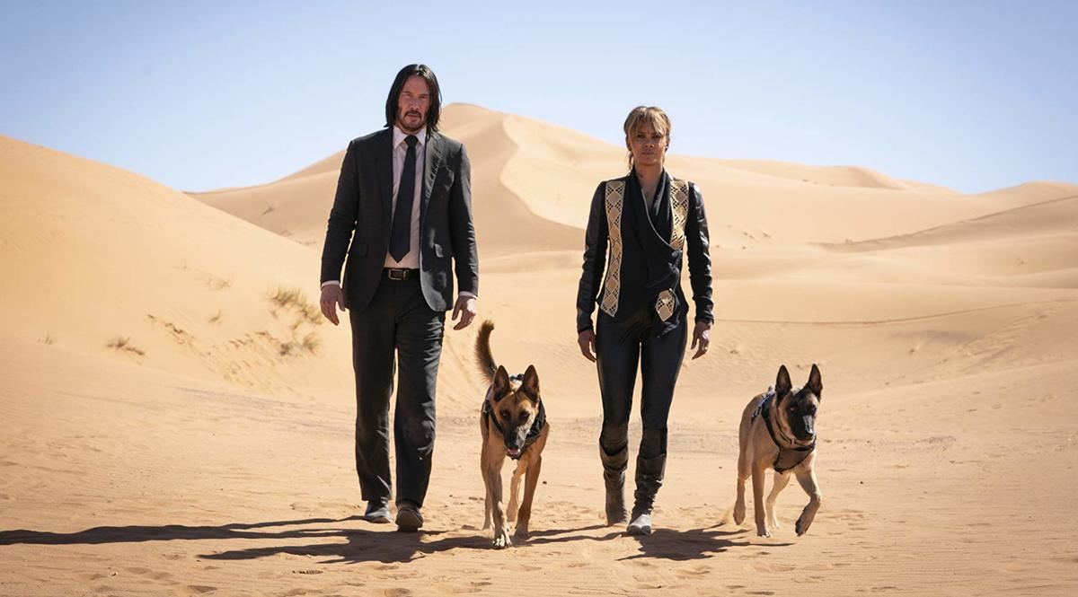 keanu reeves and halle berry walking in a desert with two german shepards
