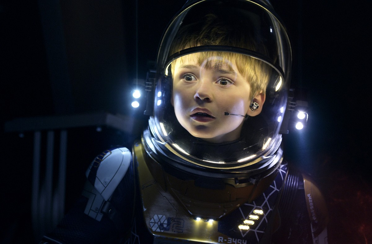 A boy in a spacesuit looks worried.