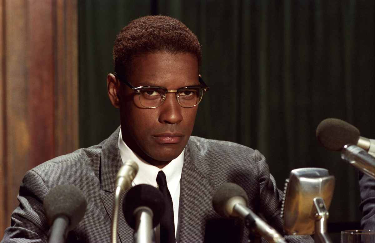 Denzel Washington wears glasses and a serious look while sitting at a press conference.