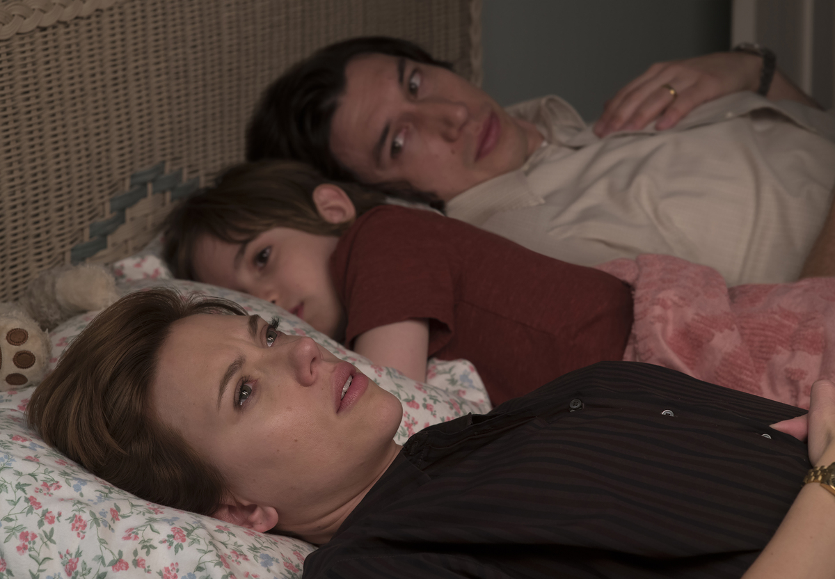 A woman lies in bed with her husband and son looking worried.