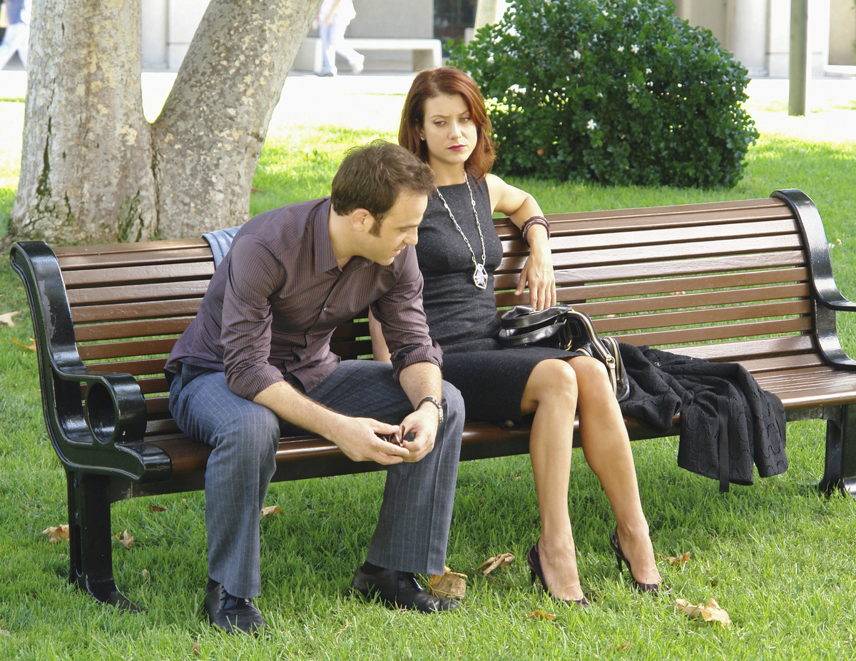 A man and woman sit next to one another on a park bench looking serious.