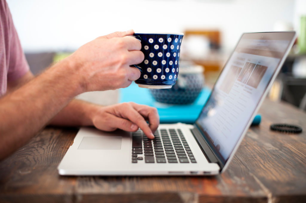 A computer user with a coffee mug is seen in this photo illustration