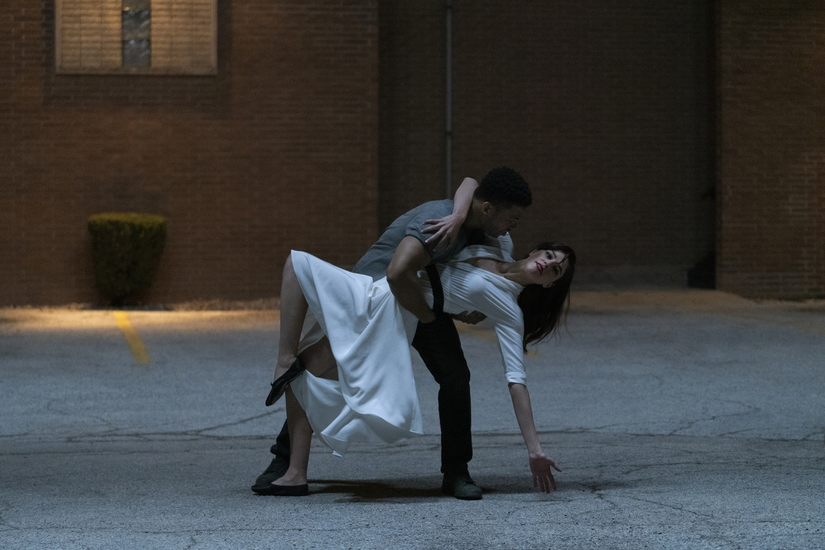 A man dips a woman as they dance outside at night.