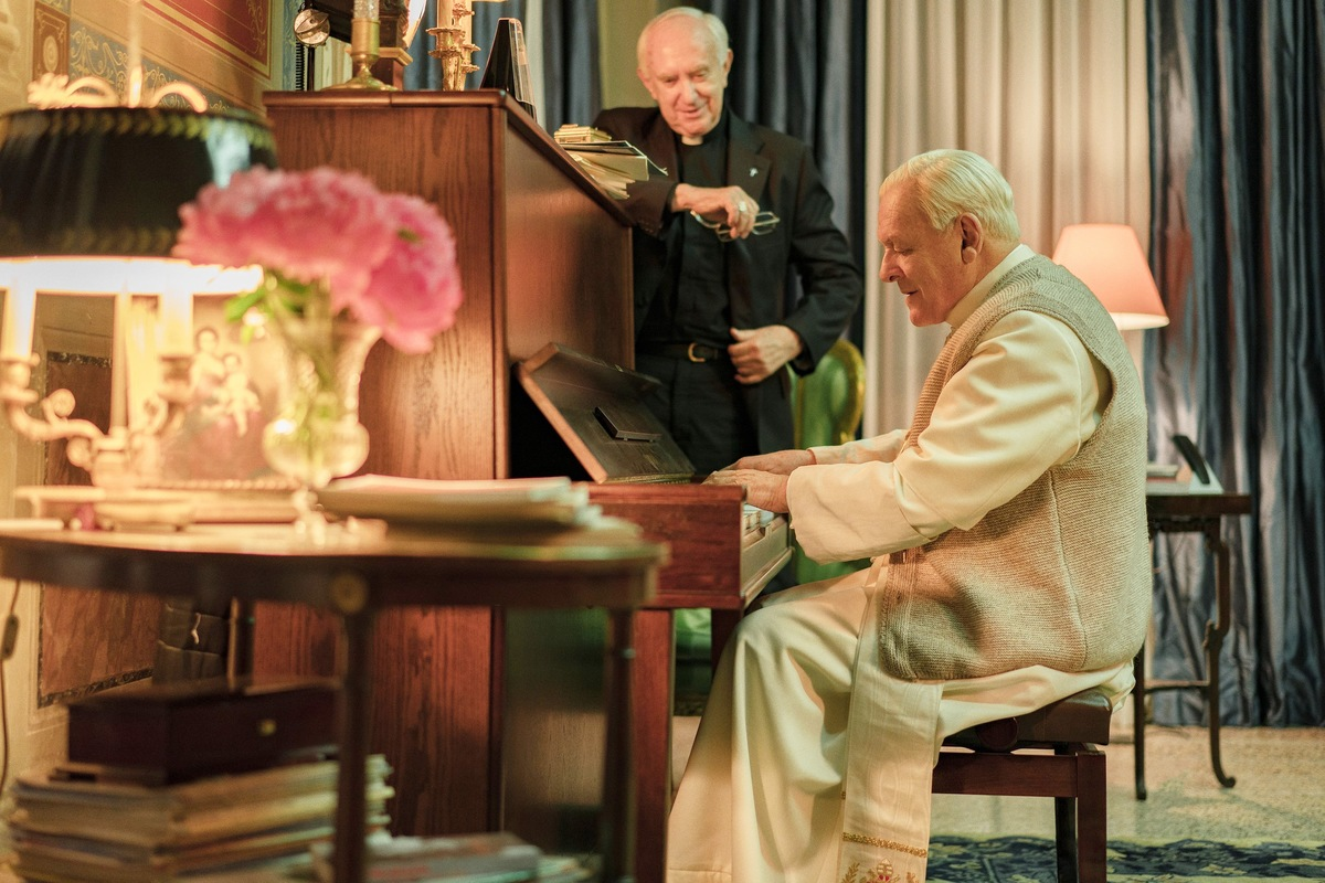 The pope plays piano while the future pope watches and smiles.