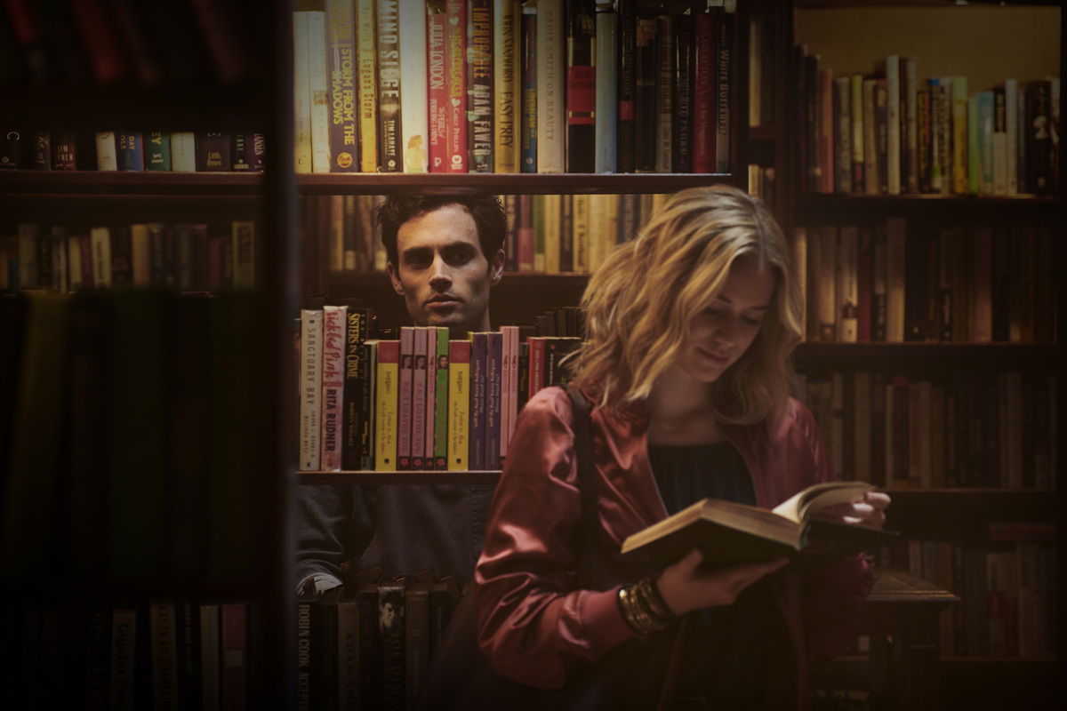 A man looks through a bookshelf at a woman who is reading.