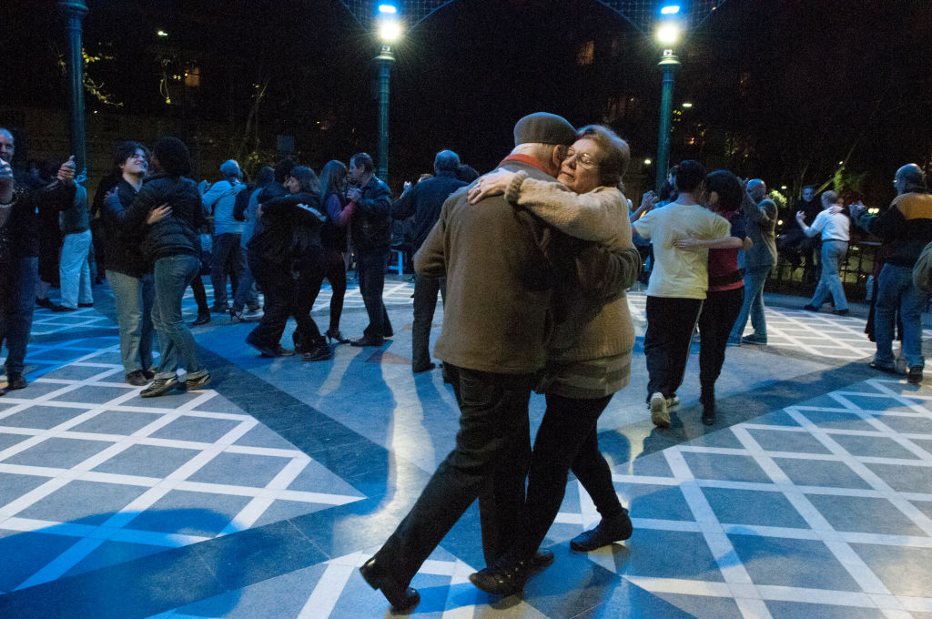 An older couple dances the Tango at night.