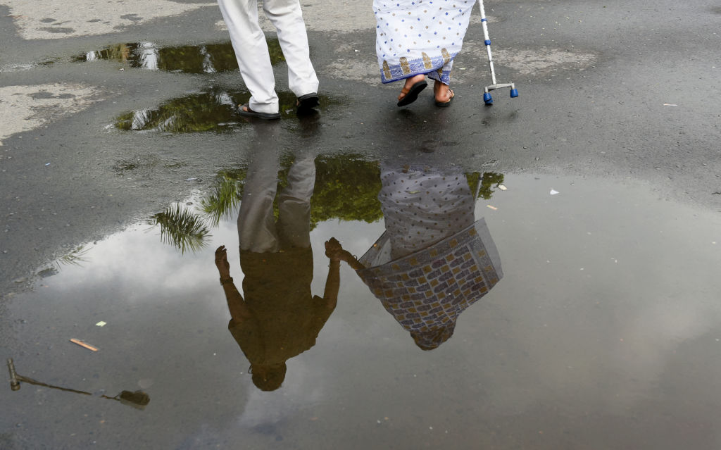 An elderly couple holds hands while crossing a wet street.