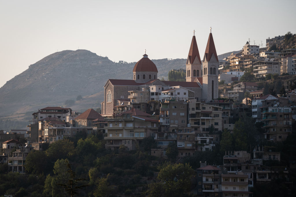 A hillside in Lebanon is full of homes surrounding a grand cathedral.