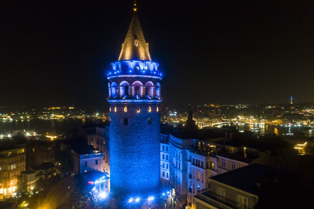 The Galata Tower in Turkey is illuminated at night by blue light.