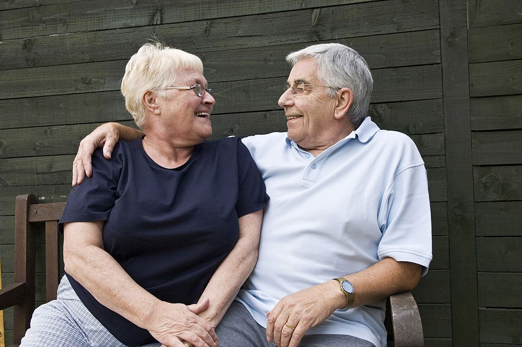 An older couple smiles at one another.