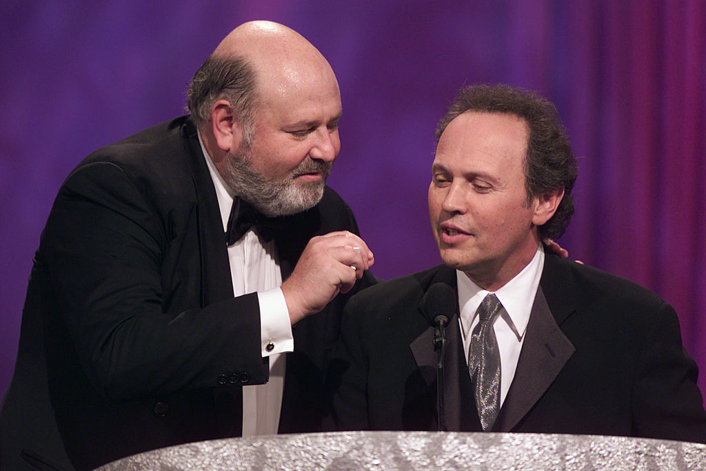 Rob Reiner and Billy Crystal stand at a podium onstage.