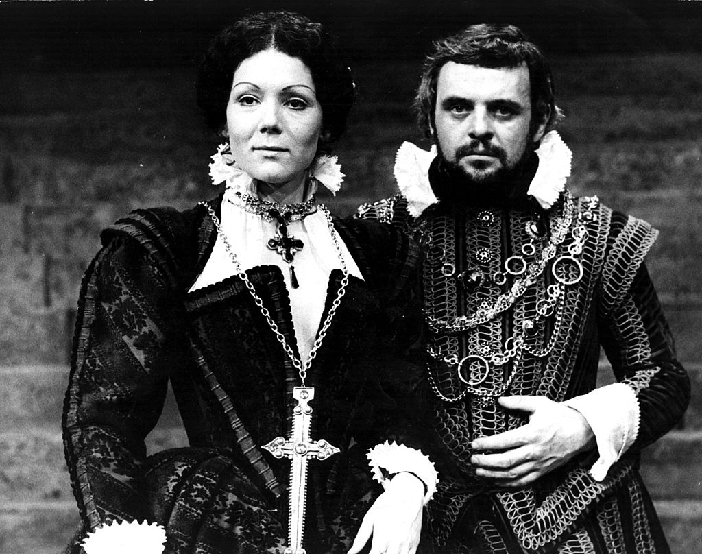 Anthony stands next to a female actor onstage while dressed in medieval attire.