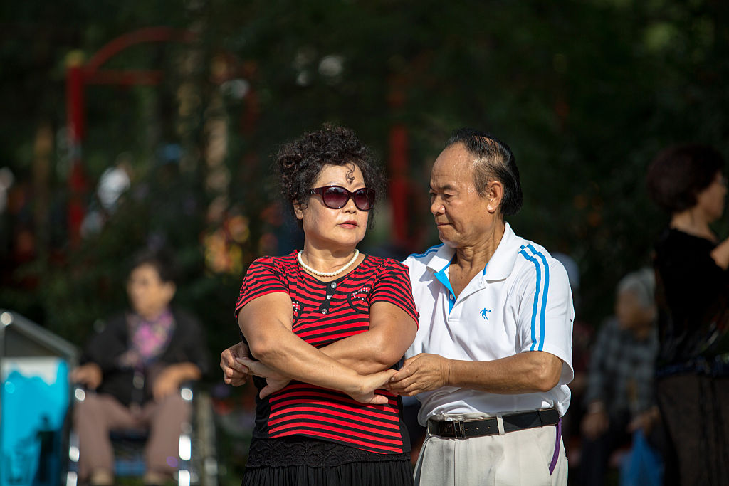A retired couple dances in the street.