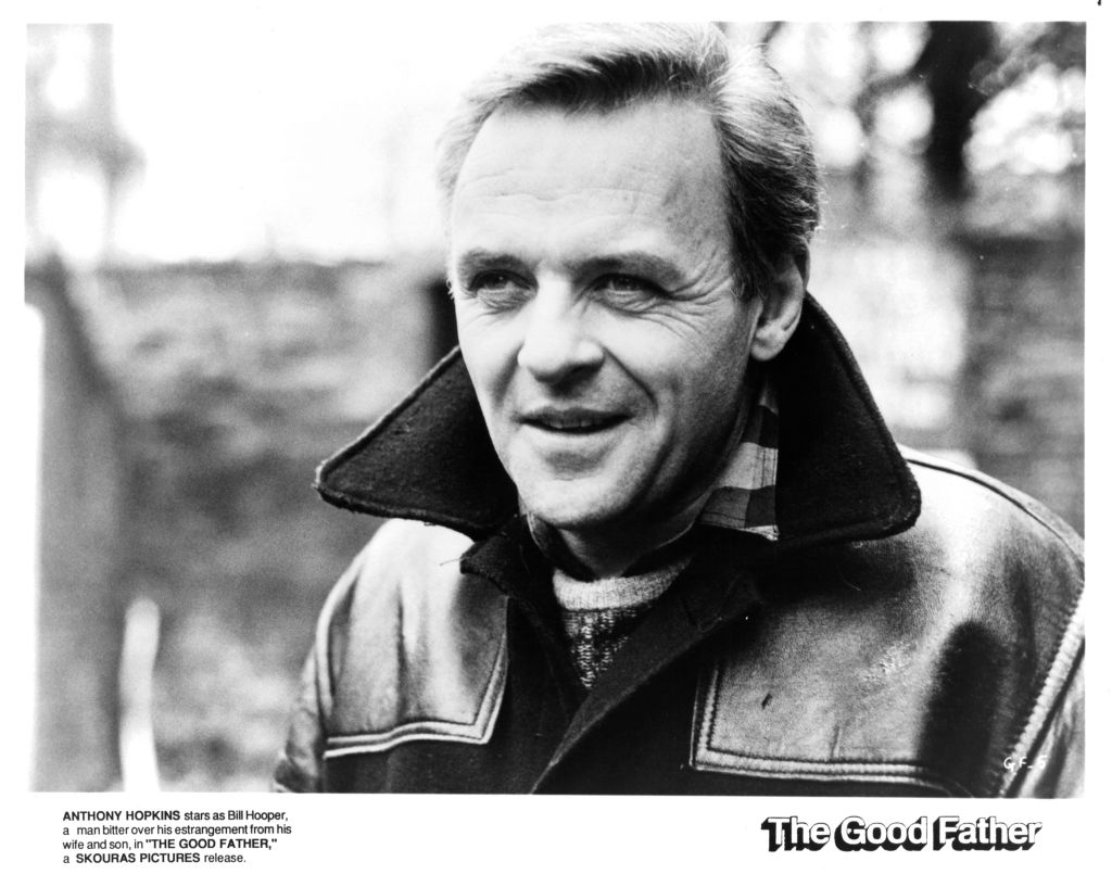 Anthony Hopkins smiles in a black and white photo.