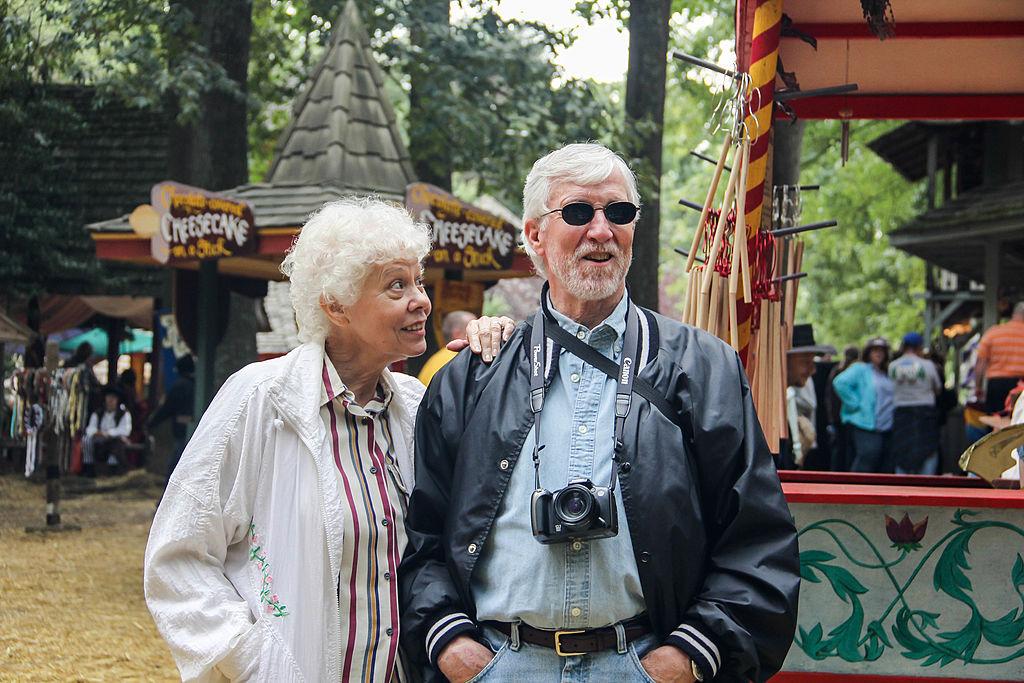 An elderly couple enjoys a festival.