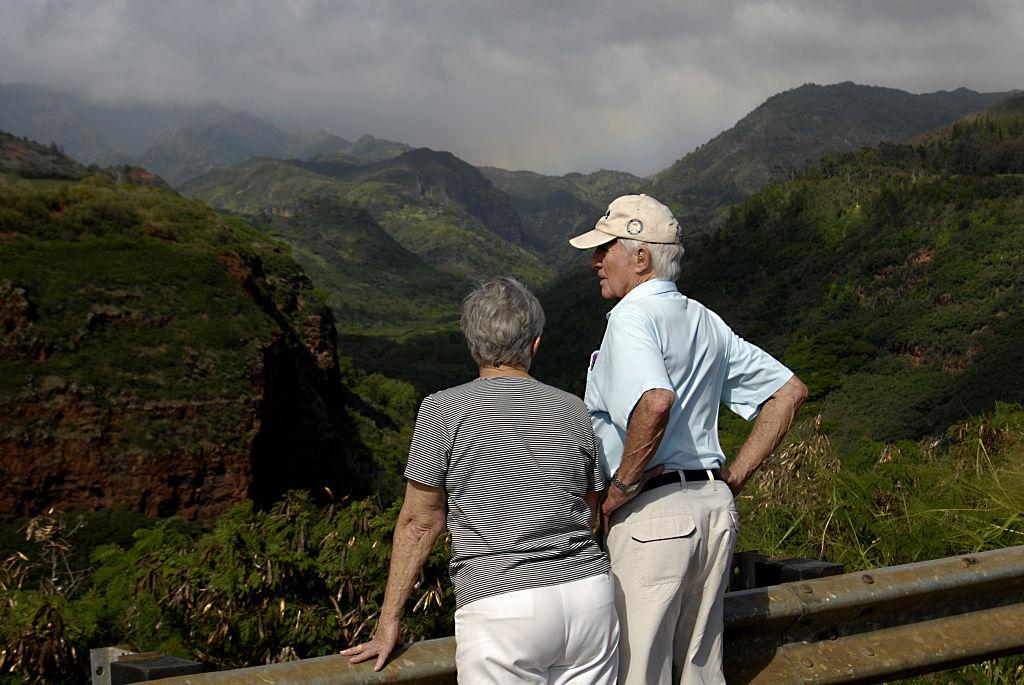 A couple overlooks a hillside.