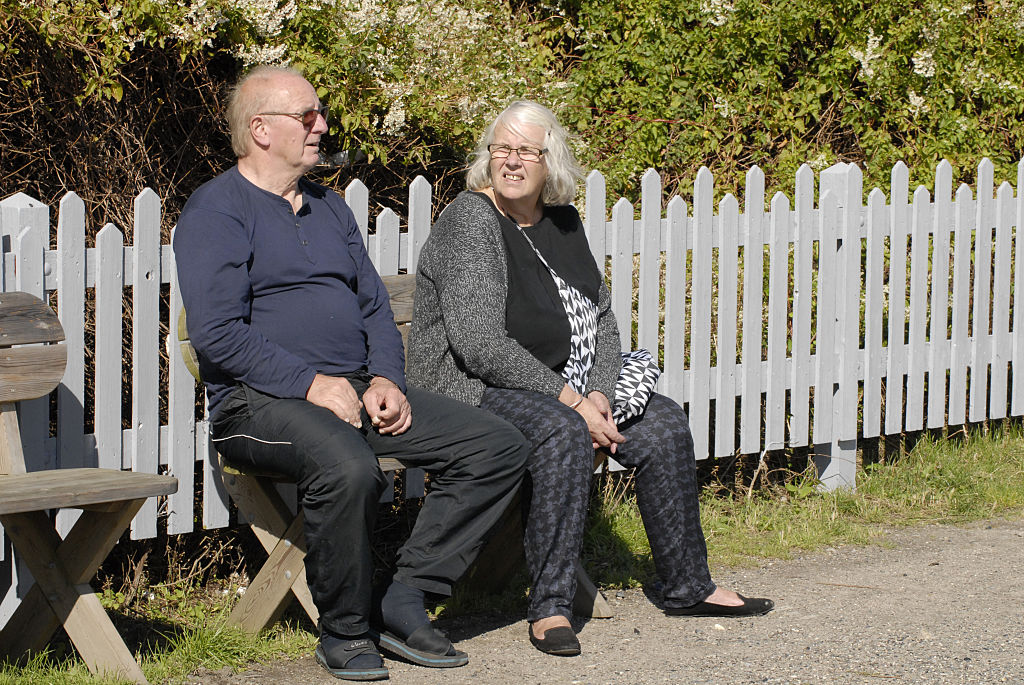 An older couple sits on a bench.